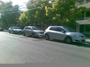 3 silver Corollas of various vintages all parked in a row